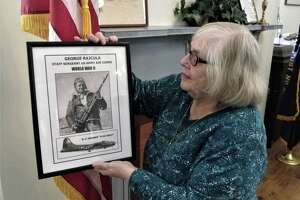Elaine Rajcula, of Brookfield, holds photograph of her brother-in-law, Staff Sgt. George Rajcula, who was killed in World War II while on a bombing mission over Germany. His story is part of a Memorial Day exhibit honoring the memory of 44 former Brookfield residents killed in military action.