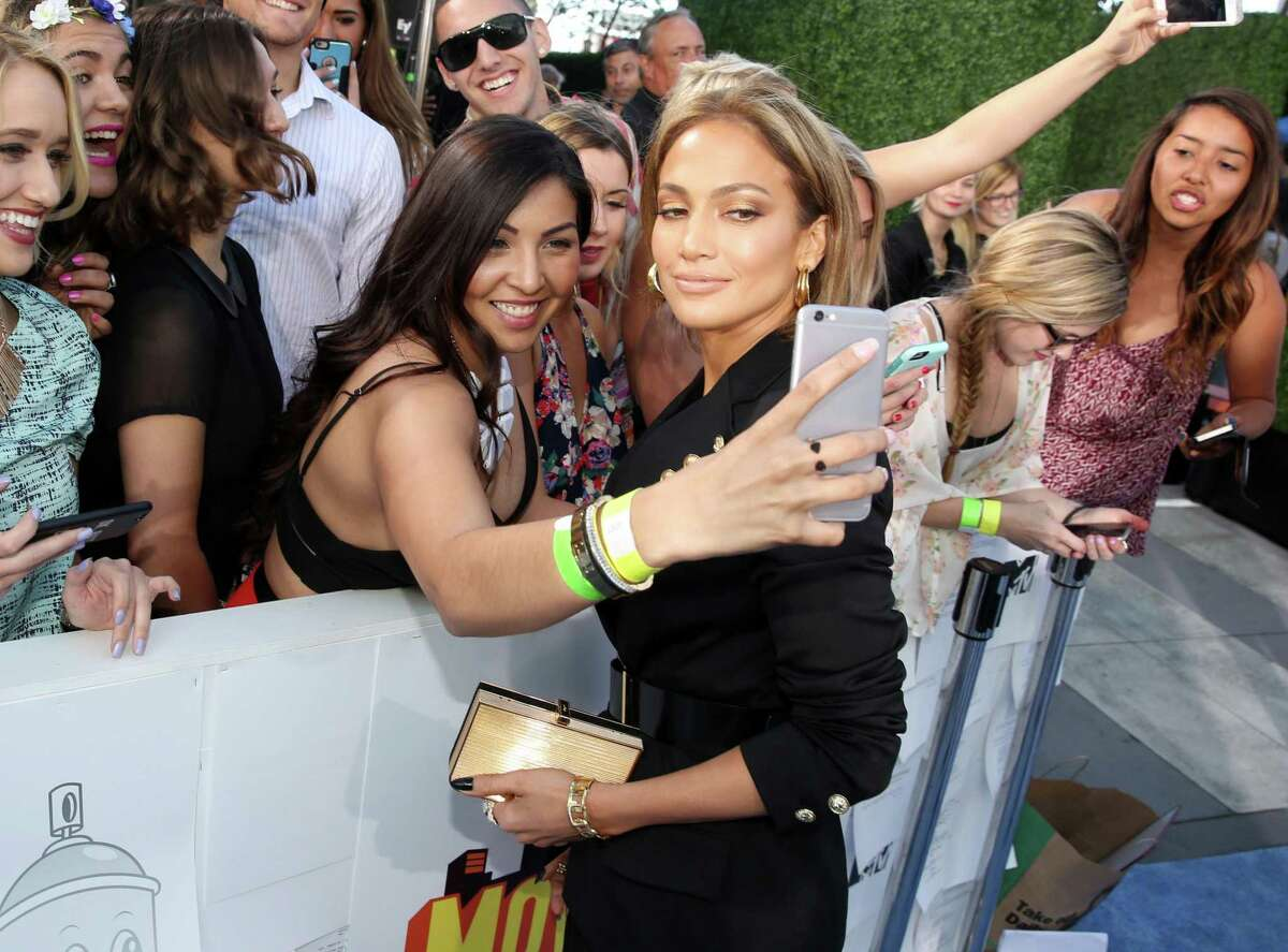 Jennifer Lopez gets her photo taken with a fan as she arrives at the MTV Movie Awards.