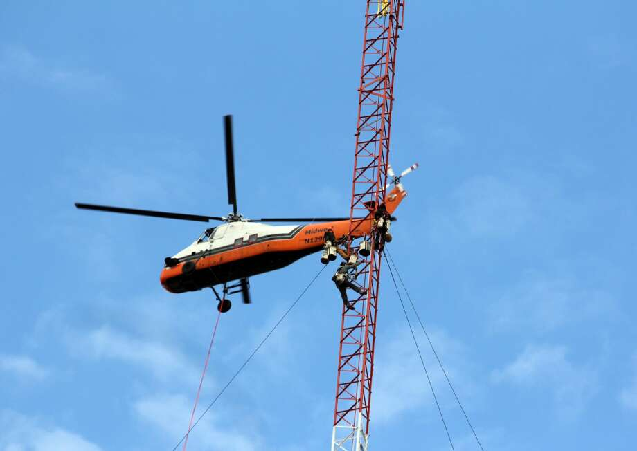 Crews worked diligently Wednesday morning to dismantle an inactive tower at North Park Campground in Harbor Beach. The 450-foot tower is being dismantled by sections via crews and a helicopter and is expected to be completed by Thursday. The tower has been inside the park for the last 60 years. Photo: Bradley Massman/Huron Daily Tribune