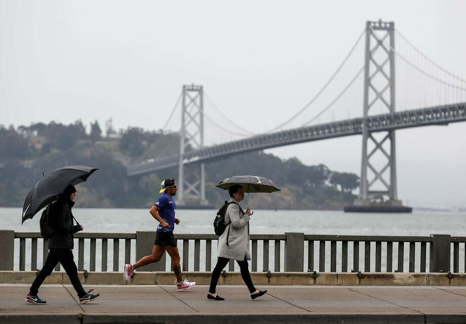 Pedestrians cover up from the rain on Wednesday, May 15, 2019 in San Francisco, Calif. Photo: Amy Osborne / Special To The Chronicle