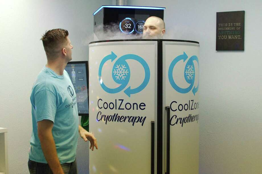 Lights are dimmed and music plays while CoolZone Cryotherapy staff member Shawn Reddy receives a treatment in a full body cryotherapy machine administered by Clint Dollens, who owns the Webster clinic. Photo: Kirk Sides / Staff Photographer / © 2019 Kirk Sides / Houston Chronicle