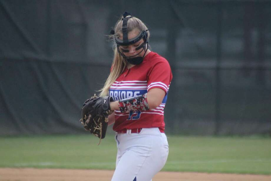 Lady Warriors pitcher Lauren Fitch looks at her arm band to see what pitch she should try and throw to the batter during Monday night's win over Northland Christian. Photo: Robert Avery