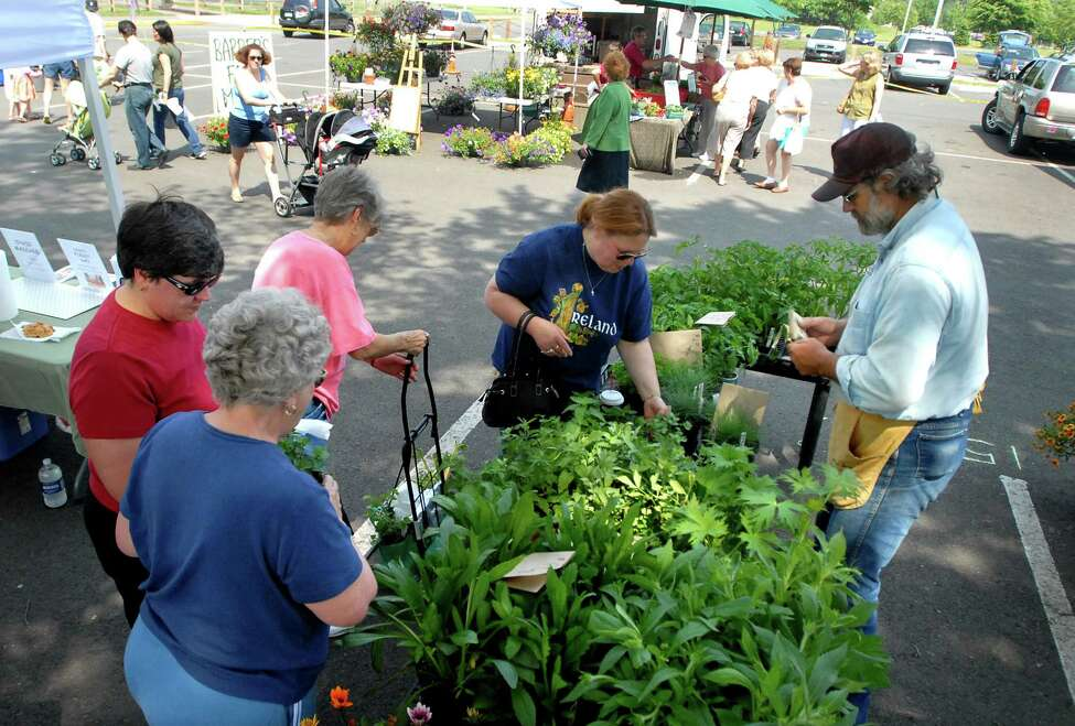 Times Union staff photo by Cindy Schultz -- Dennis Bradt of the John Burger Farm, right, assists customers with the plants, including herbs and tomatoes, for sale during the Farmer's Market on Saturday, June 7, 2008, at The Crossings in Colonie, N.Y. (WITH GISH STORY)