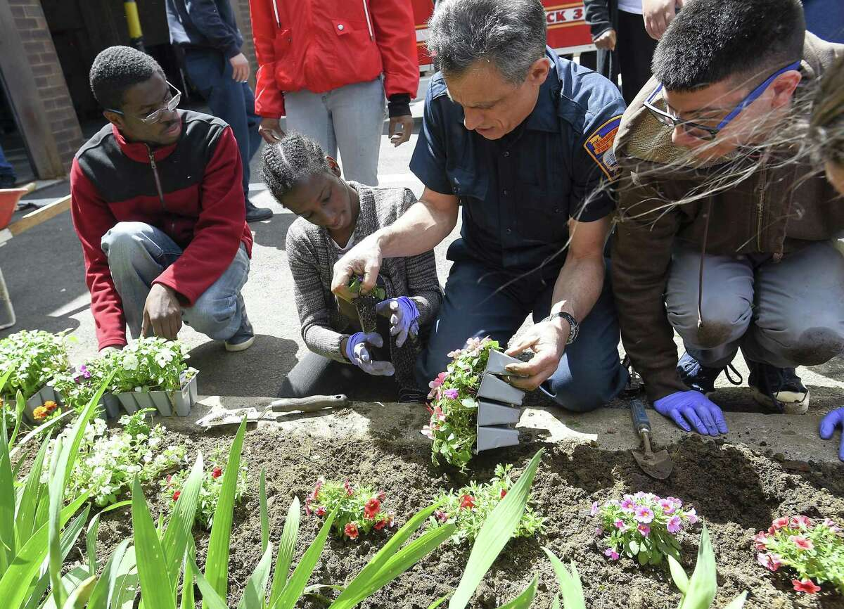 Stamford firefighter Mike Battinelli helps Christele Thomas, second from left, and other students from Stamford Public Schools Individuals Achieving Independence (IAI) program plant spring flowers at Stamford Fire Station #3 on May 15, 2019 in Stamford, Connecticut. Six students from the IAI program, along with a dozen firefighters spent the day planting flowers and shrubs to beautify the firehouse grounds. This is the fourth year that Stamford Public Schools Social Worker Laura Marino and Engine 3 Stamford Firefighter Tony Marino have paired individuals with firefighters to help learn life and vocational skills.