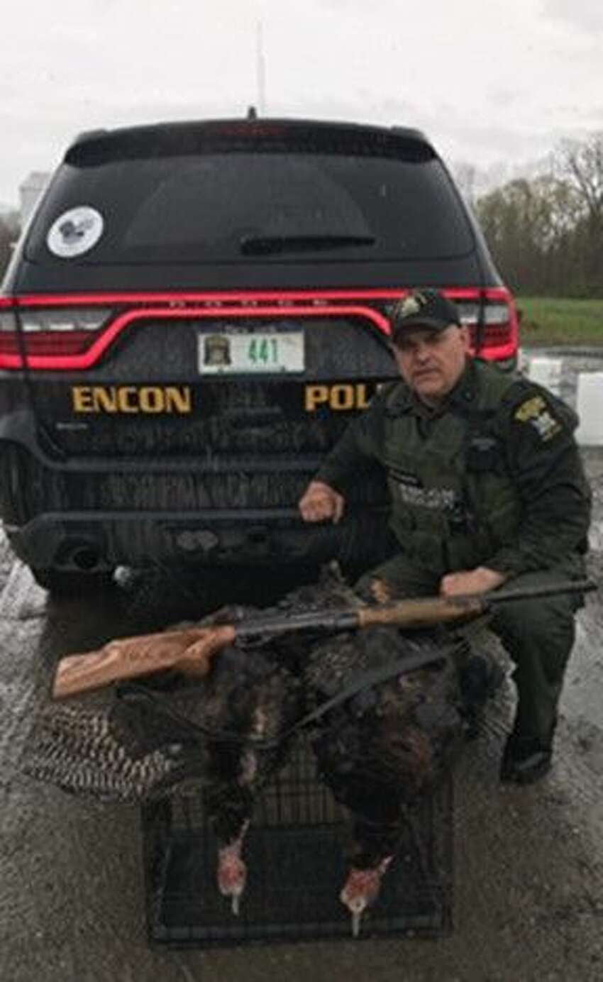 State Environmental Conservation Officer Brian Canzeri poses with two illegally hunted turkeys and a shotgun, all of which was seized as evidence, following a May 3, 2019, investigation in Petersburg, N.Y.