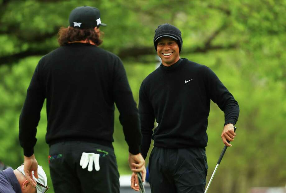 Tiger Woods, right, smiles with Pat Perez on the practice green during a practice round prior to the PGA Championship at the Bethpage Black course on Tuesday. Photo: Mike Ehrmann / Getty Images / 2019 Getty Images
