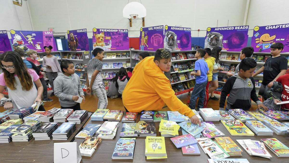Ricardo Mazas, a fifth-grader at Northeast School browses a table of books as he and fellow students shop for books at Northeast's annual Scholastic Spring Book Fair on May 15, 2019 in Stamford, Connecticut. Proceeds from the event raise over $2500 to help pay for field trips, bus transportation, enrichment programs for over 600 students at the school.