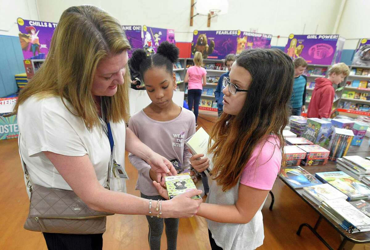 Sarah Fullilove, a fifth-grade teacher at Northeast Elementary School, helps students Nylise Dyson and Taylor Troy as they shop for books at the school's annual Scholastic Spring Book Fair on May 15, 2019 in Stamford, Connecticut. Proceeds from the event raise over $2500 to help pay for field trips, bus transportation, enrichment programs for over 600 students at the school.