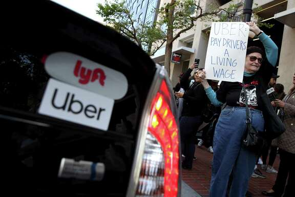 A supporter of ride share drivers from Uber and Lyft holds a sign during a protest in front of Uber headquarters May 8 in San Francisco, Calif. A reader says Uber and Lyft drivers should just quit.