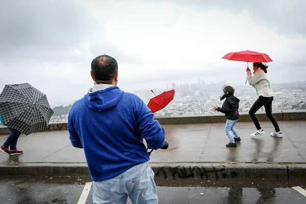 Rudranshi Ganatra, 5, looses her umbrella to the wind as sister Hetal, 16, and father Hiten react at Twin Peaks on Wednesday, May 15, 2019 in San Francisco, Calif.