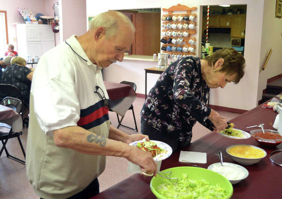 Dennis Johnson, left, and his wife Nancy Johnson, from Holiday Shores, fix tacos during Wednesday's taco dinner at St. Thomas Episcopal Church in Glen Carbon. Photo: Scott Marion| The Intelligencer