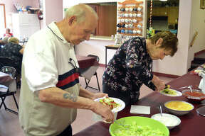 Dennis Johnson, left, and his wife Nancy Johnson, from Holiday Shores, fix tacos during Wednesday's taco dinner at St. Thomas Episcopal Church in Glen Carbon.