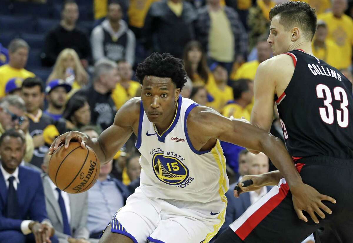 Golden State Warriors' Damian Jones drives past Portland Trail Blazers' Zach Collins in 4th quarter of Warriors' 116-94 win in Game 1 of NBA Western Conference Finals at Oracle Arena in Oakland, Calif., on Tuesday, May 14, 2019.