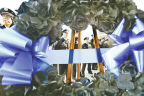 Wood River Police officers line up Wednesday, as seen through a wreath, at a memorial service for National Police Memorial Day at the new Wood River police station. A ribbon was also cut to officially dedicate the recently opened station. Two Wood River police officers, who both died on the job more than 100 years ago, were remembered at the ceremony with grandchildren and great grandchildren in attendance. About 100 people attended the memorial service including the Madison County sheriff, state's attorney, local politicians and several retired area police officers.