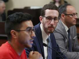 State Sen. Scott Wiener, D-San Francisco, center, listens as Rene Moya, left, director of Housing Is A Human Right, testifies against Wiener's housing measure Wednesday, April 24, 2019, in Sacramento, Calif. Wiener's bill, SB50, that would increase housing near transportation and job hubs was approved by the Senate Governance and Finance Committee, after it was merged with SB4, a measure by State Sen. Mike McGuire, D-Healdsburg. (AP Photo/Rich Pedroncelli)