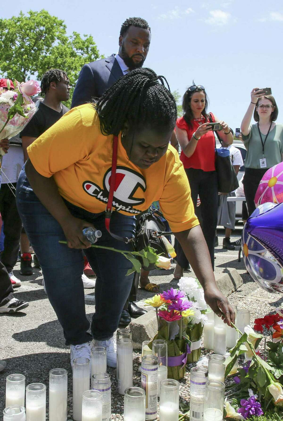 Chelsie Rubin drops off a rose at the memorial for her mother, Pamela Turner, at The Brixton Apartments complex Wednesday, May 15, 2019, in Baytown, Texas. Turner was killed Monday night during a confrontation with a Baytown Police officer.