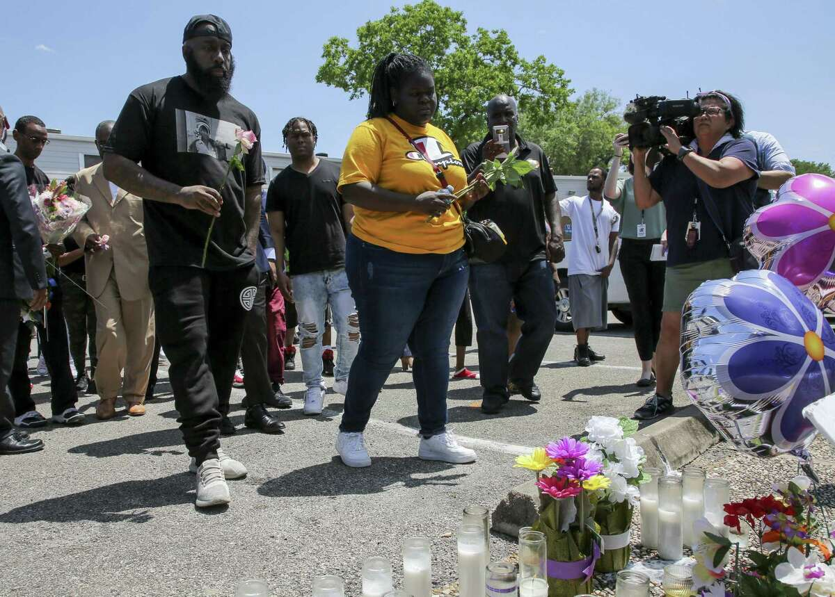 Chelsie Rubin, center, alongside with Houston rapper Trae tha Truth, left, drop off roses at the memorial for her mother, Pamela Turner, at The Brixton Apartments complex Wednesday, May 15, 2019, in Baytown, Texas. Turner was killed Monday night during a confrontation with a Baytown Police officer.