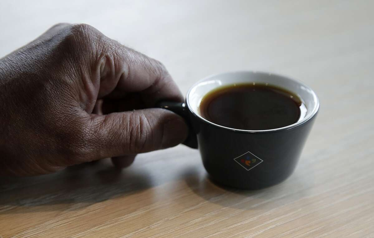 Klatch Coffee owner Bo Thiara holds a cup of Elida Natural Geisha coffee at his shop in San Francisco, Wednesday, May 15, 2019. The California cafe is brewing up what it calls the world's most expensive coffee - at $75 a cup. Klatch Coffee Roasters is serving the exclusive brew, the Elida Natural Geisha 803, at its branches in Southern California and San Francisco. (AP Photo/Jeff Chiu)