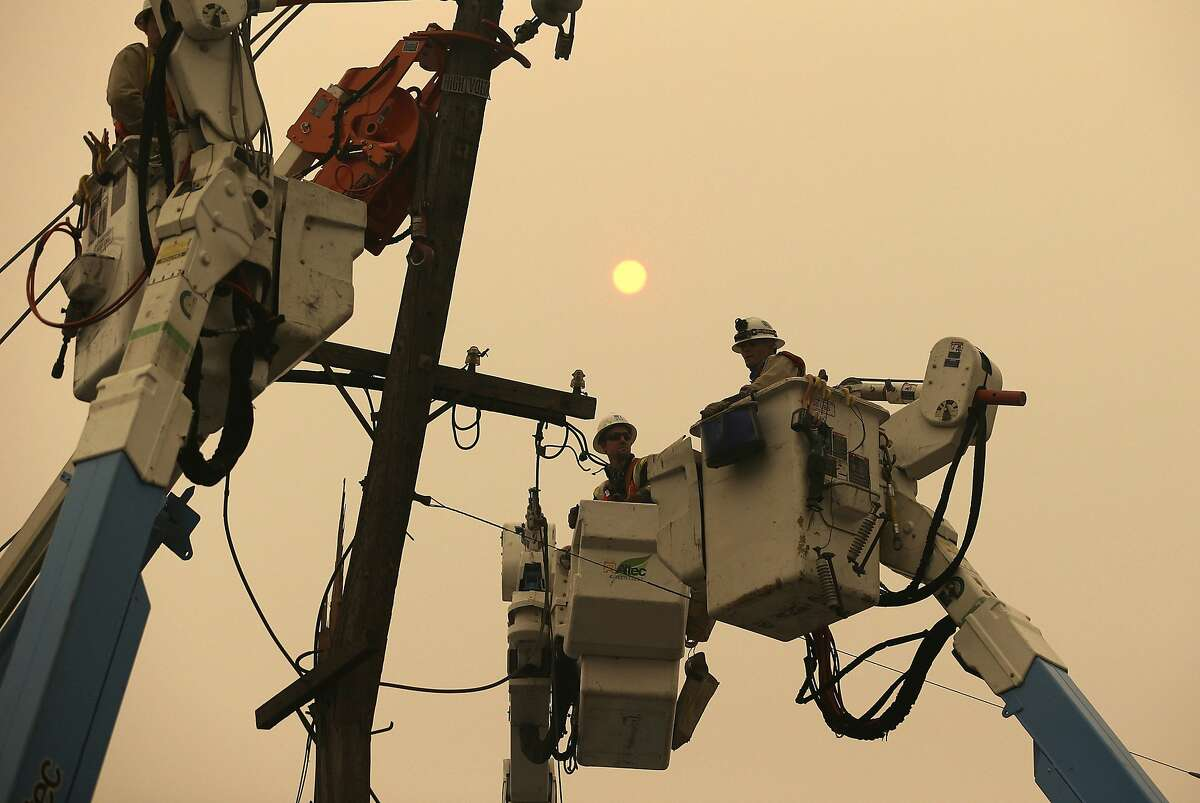 In this Nov. 9, 2018 file photo, Pacific Gas & Electric crews work to restore power lines in Paradise, Calif.