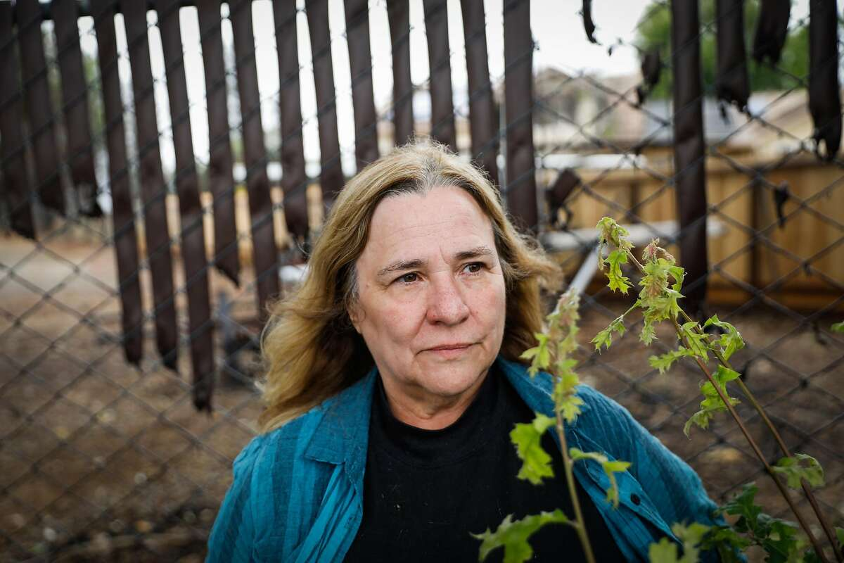 """Paradise resident Susan Doyle stands for a portrait outside Town Hall in Paradise, California, on Wednesday, May 15, 2019. Doyle lost her house in the Camp Fire in November 2018. After reading a news alert on her phone about the PG&E being the cause of the Camp Fire Doyle said, """"We've all known it was PG&E from the beginning. It's just official now. It doesn't make me feel better at all. I'm pissed off. I worked my whole life for my home. It's not just the stuff in it. It's my community. I'm bitter about this whole fire. It took my life. How can I come back to this?"""""""