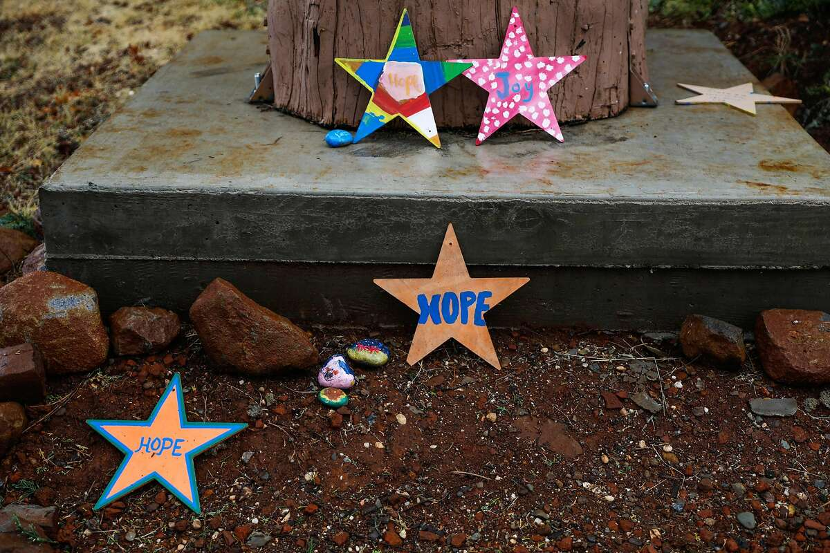 """Small stars saying """"Hope"""" and """"Joy"""" lay on the ground outside of the Paradise Police station in Paradise, California, on Wednesday, May 15, 2019."""