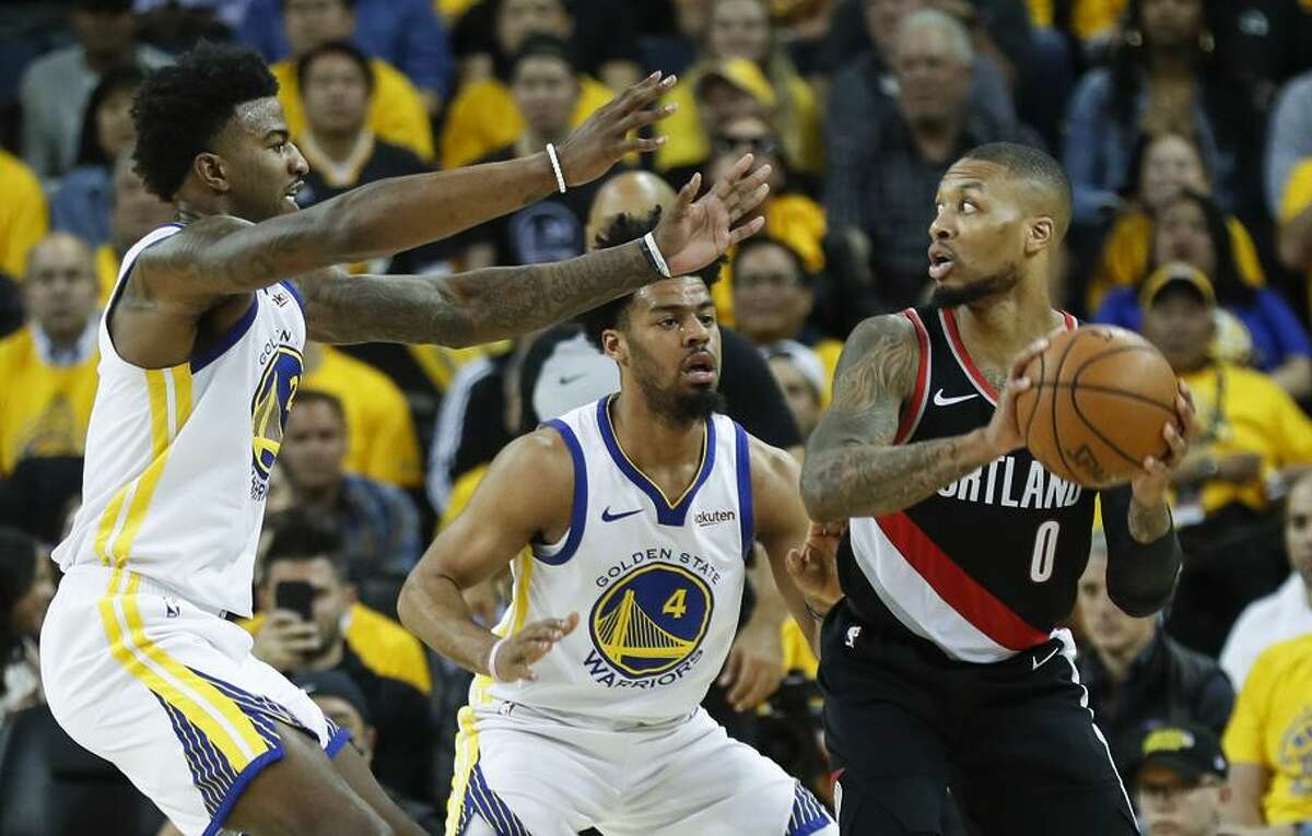 Warriors Jordan Bell (left) and Quinn Cook defend against the Trail Blazers' Damian Lillard during Game 1 in Oakland.