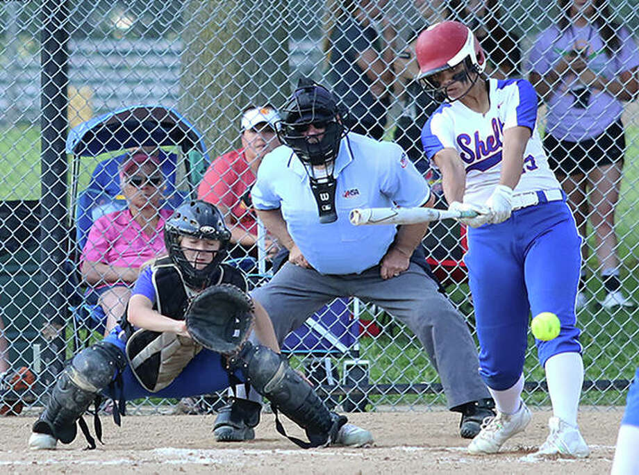 Roxana's Alyssa Luck (right) singles to left field while Marquette catcher Jada Johnson and the plate umpire look on Wednesday in a Southwestern Class 2A Regional semifinal at Moore Park in Alton. Photo: Greg Shashack / The Telegraph