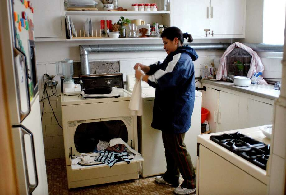 Gabriela Garcia, 24, who works as a maid in a home, washes clothes, Jan. 20, 2003, in Mexico City. Mexico remains in the dark ages when it comes to the treatment of domestic workers, despite repeated efforts by activists to reform antiquated labor laws and President Vicente Fox's recent promises to improve conditions for women workers. (AP Photo/Marco Ugarte) Photo: Marco Ugarte /AP / AP