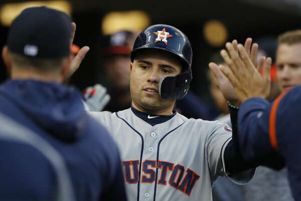 Houston Astros' Aledmys Diaz is greeted in the dugout after scoring during the fourth inning of a baseball game against the Detroit Tigers, Wednesday, May 15, 2019, in Detroit. (AP Photo/Carlos Osorio)
