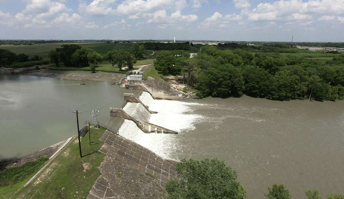 The dam on Lake Dunlap continues to spill water on May 15, 2019, the day after a middle spillway gate gave way. Much of the lake is draining.