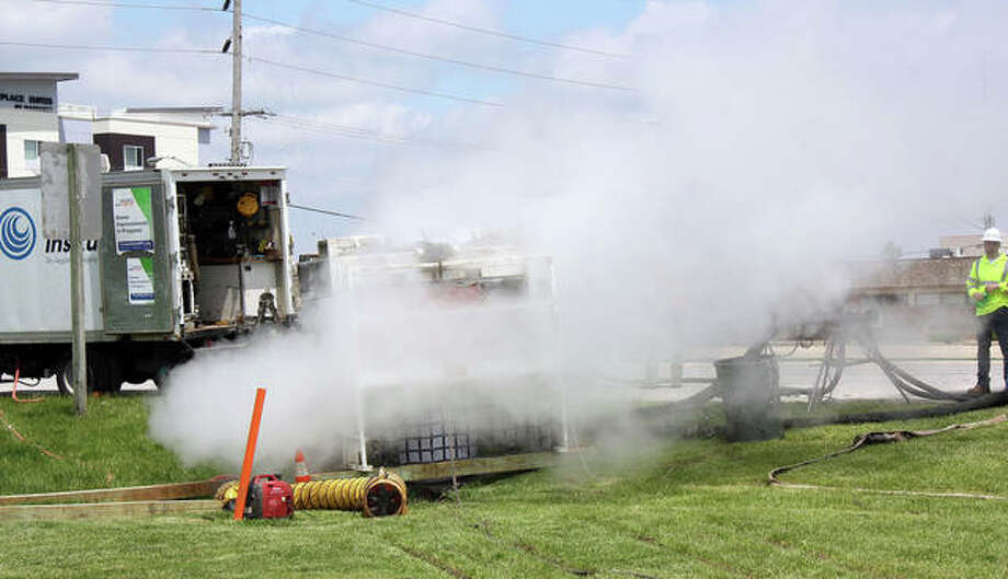 Steam billows into the atmosphere at the southwest corner of Route 157 and Center Grove Road Wednesday as Insituform construction crews applied a lining to a storm sewer in front of Kettle River Furniture. The right southbound lane of Route 157 was blocked between Commerce Drive and Center Grove and the left-turn lane from westbound Center Grove to southbound Route 157 was temporarily closed during the one-day project. Photo: Charles Bolinger | The Intelligencer