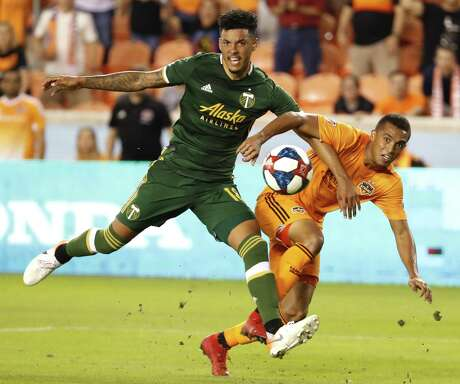 Dynamo forward Mauro Manotas, right, gets off a shot despite the efforts of Timbers defender Julio Cascante.