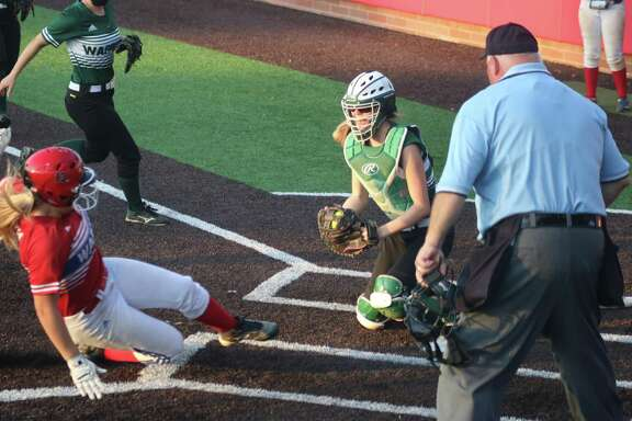 FBCA's Lauren Fitch becomes an out at home plate as the Lady Warriors tried to surprise The Woodlands Christian with a fourth-inning squeeze play. Mattie Hopkins is the catcher.