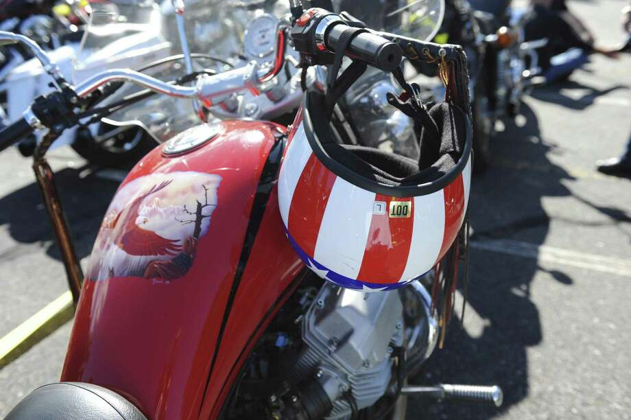 A red motorcycle and a red helmet at the 12th Annual CT United Ride Sunday, Sept. 9, 2012. The ride starts in Norwalk with a ceremony of 9/11 tribute then a ride through 11 towns with police motorcycle escorts ending with a 5 mile parade through Bridgeport and ends in Bridgeport at the beach. beach. Photo: Helen Neafsey / Helen Neafsey / Greenwich Time