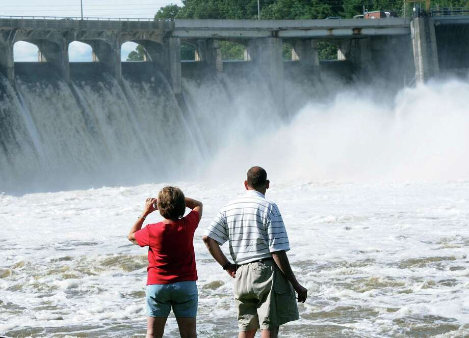 Onlookers watch the raging waters over the Stevenson Dam. Photo: File Photo