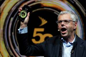Michel Combes, CEO of Sprint, holds the new LG V50 ThinQ 5G smartphone during its presentation at the Mobile World Congress, in Barcelona, Spain, Sunday, Feb. 24, 2019. The fair started with press conferences on Sunday, before the doors open on Monday, Feb. 25, and runs until Feb. 28. (AP Photo/Manu Fernandez)