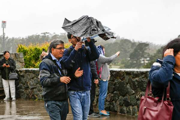 A man fumbles with his umbrella as he tries to cover from the rain at Twin Peaks on Wednesday, May 15, 2019 in San Francisco, Calif.