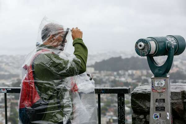 A man uses a poncho to cover from the rain at Twin Peaks on Wednesday, May 15, 2019 in San Francisco, Calif.