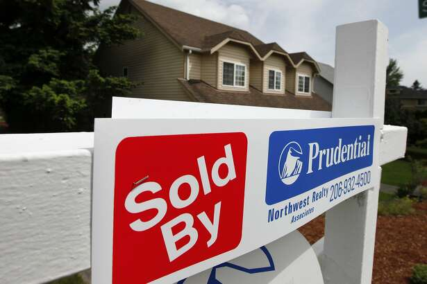 "FILE - In this June 9, 2011 file photo, a ""sold"" notice is posted on the ""for sale"" sign of a house, in Seattle.Home prices in major U.S. cities have risen for the first time in eight months, boosted by an annual flurry of spring buyers. (AP Photo/Elaine Thompson, file)"