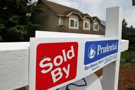 """FILE - In this June 9, 2011 file photo, a """"sold"""" notice is posted on the """"for sale"""" sign of a house, in Seattle.Home prices in major U.S. cities have risen for the first time in eight months, boosted by an annual flurry of spring buyers. (AP Photo/Elaine Thompson, file)"""