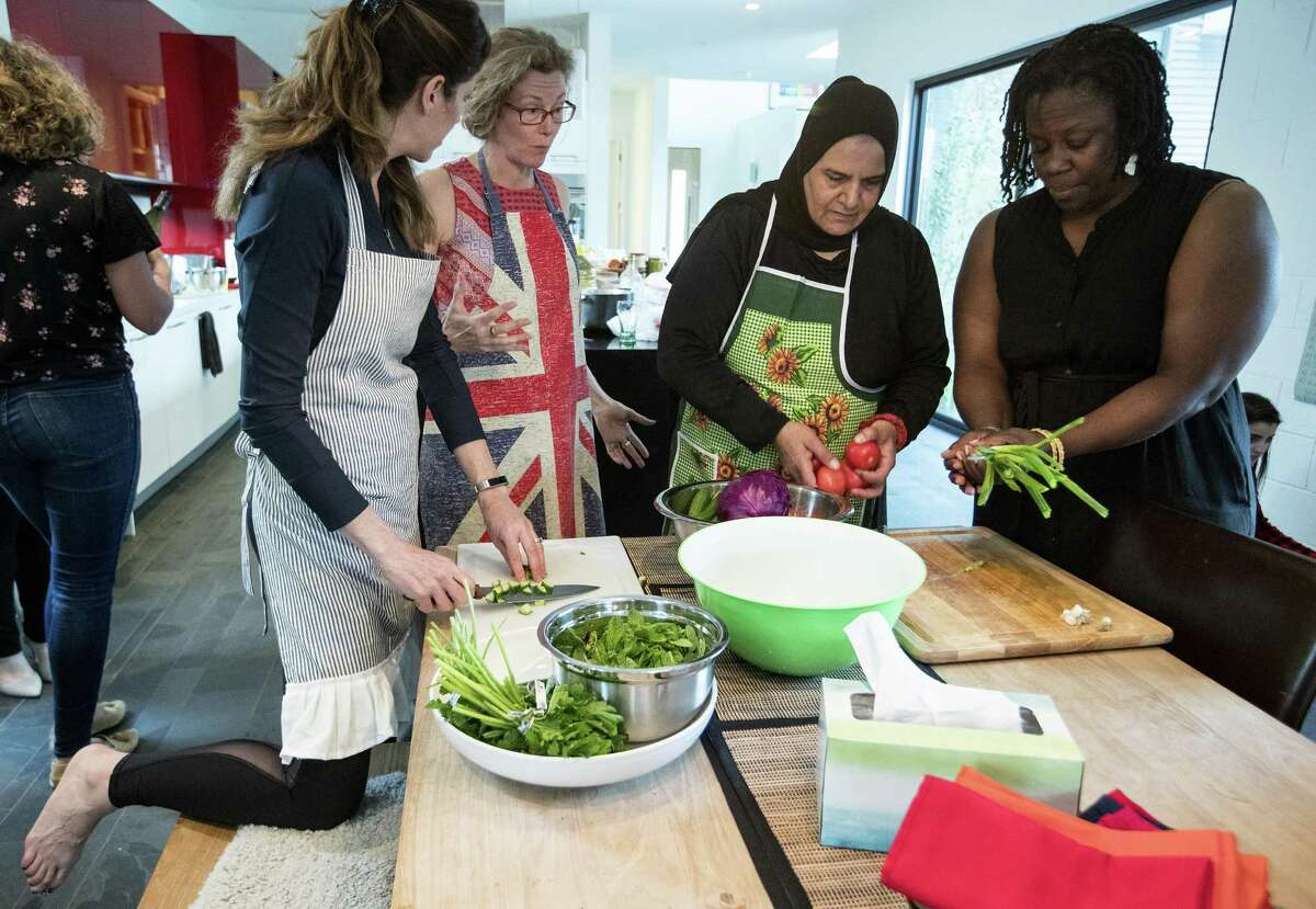 Michelle Jennings, left, Sophy Ashworth, Wafdia ibrahim and Valerie Cramer prepare vegetables during a dinner party, featuring foods from Syria, on Saturday, March 23, 2019, at Ashworth's home in Houston. Ibrahim sought refuge in the U.S. from Homs, Syria, about three years ago, and has since found that cooking has been her best option to to earn a living. She has started private cooking classes for native Houstonians in her and their homes.
