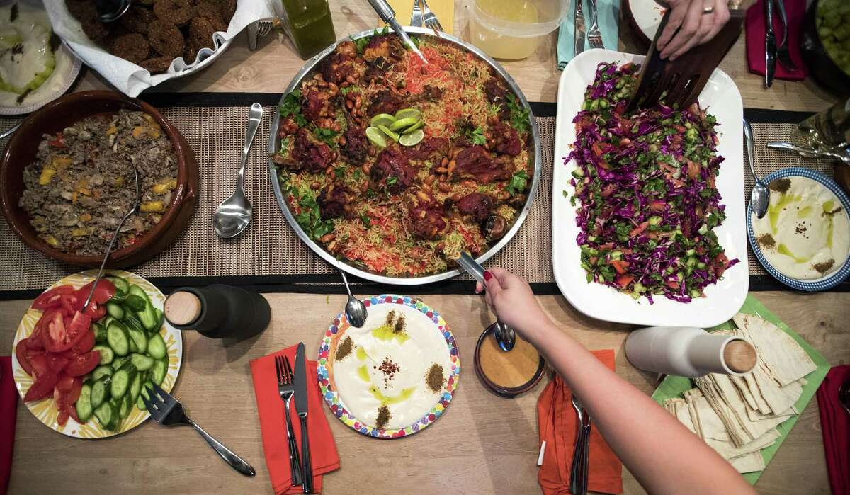 Sophy Ashworth's dinner guests dish up their plates during a dinner party, featuring foods from Syria, on Saturday, March 23, 2019, in Houston. Wafdia Ibrahim sought refuge in the U.S. from Homs, Syria about three years ago, and has since found that cooking has been her best option to to earn a living. She has started private cooking classes for native Houstonians in her and their homes.