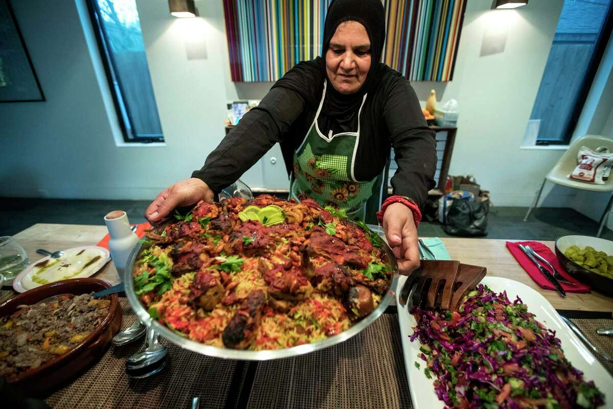 Wafdia Ibrahim places Mandi on the table during a dinner party, featuring foods from Syria, on Saturday, March 23, 2019, in Houston. Ibrahim sought refuge in the U.S. from Homs, Syria about three years ago, and has since found that cooking has been her best option to to earn a living. She has started private cooking classes for native Houstonians in her and their homes.