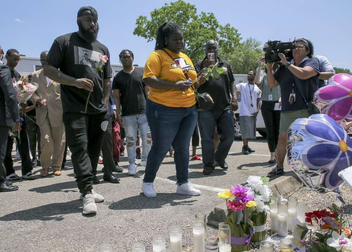 Chelsie Ruben, center, alongside with Houston rapper Trae the Truth, left, drop off roses at the memorial at the Brixton Apartments complex in Baytown, Texas, Wednesday, May 15, 2019, for her mother, Pamela Turner, who was killed Monday night during a confrontation with a Baytown Police officer. (Godofredo A Vasquez/Houston Chronicle via AP)