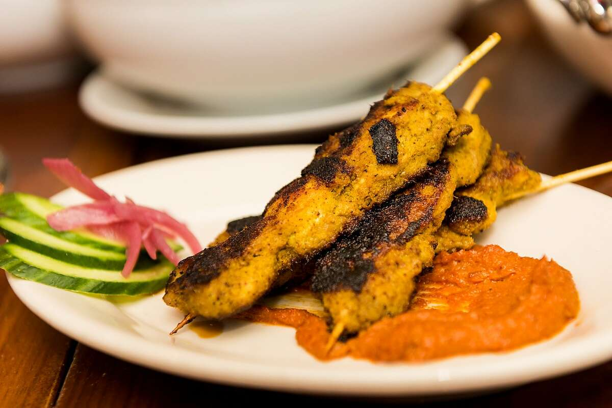 Chicken satay is served at Local Kitchen with pickled onions, cucumber and peanut sauce.