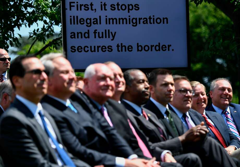 Cabinet members and Senators look on as President Trump announces a new immigration plan at a Rose Garden ceremony. The proposal has yet to be embraced by his own party. Photo: Brendan Smialowski / AFP / Getty Images