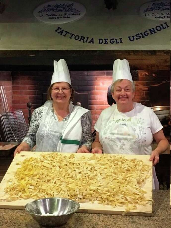 The author, Donna Frawley, right,and her friend Irene hold up a cutting board with the entire group's handmade pasta during a past class in Italy. (Donna Frawley/for the Daily News)