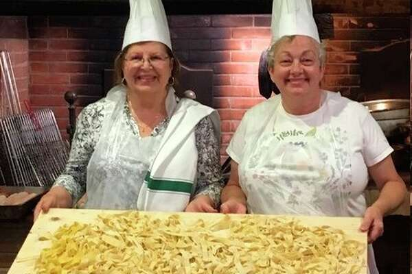 The author, Donna Frawley, right, and her friend Irene hold up a cutting board with the entire group's handmade pasta during a past class in Italy. (Donna Frawley/for the Daily News)
