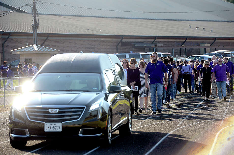 Family and football players and coaches follow as the hearse carrying coach W. T. Johnston's casket enters the stadium during a memorial service for the 2-time state champion Newton football coach. Photo: Kim Brent/The Enterprise
