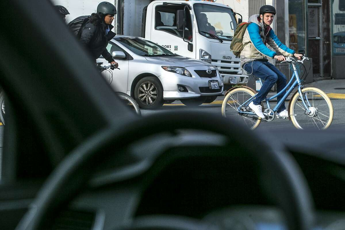 A bicyclist checks out Uber's self-driving Volvo XC90 SUV on Tuesday, Dec. 13, 2016 in San Francisco, Calif.